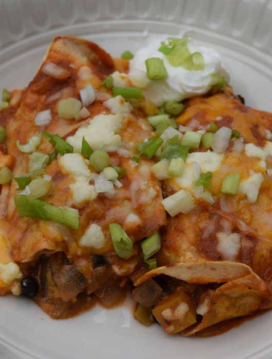 two black bean enchiladas with chopped scallions and sour cream in a white bowl