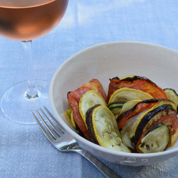 glass of wine and bowl of roasted summer vegetables