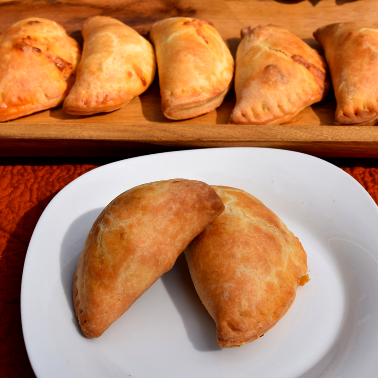 serving tray of empanadas with close up on a white plate