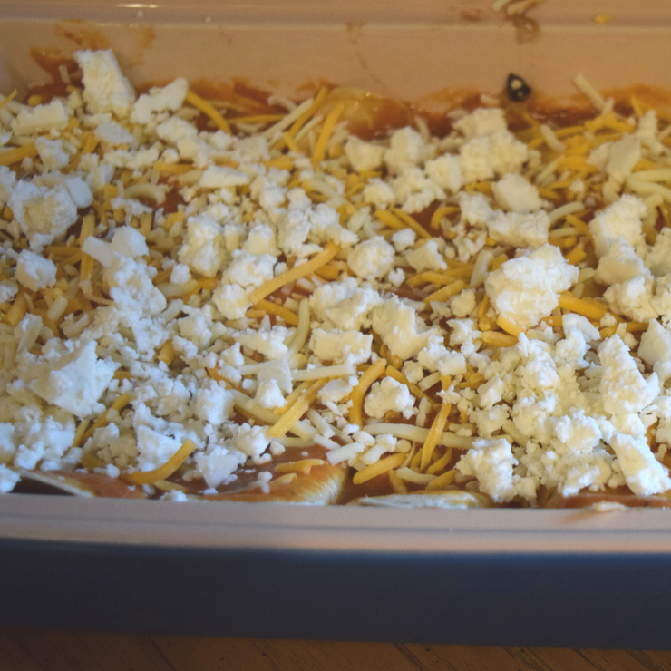 cheese topping of a tray of enchiladas before baking