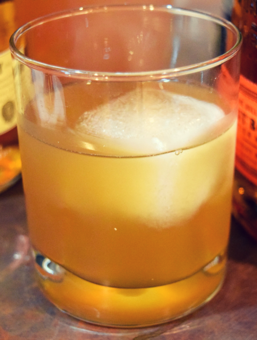 old fashioned glass with a square ice cube and cocktail