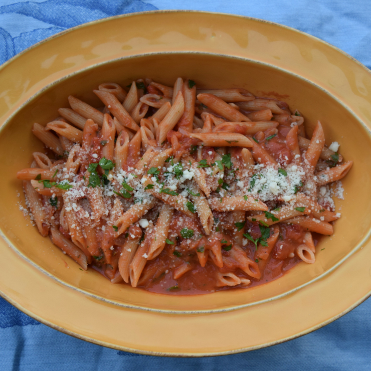 yellow ceramic bowl of pasta with vodka sauce sprinkled with parmesan and parsley