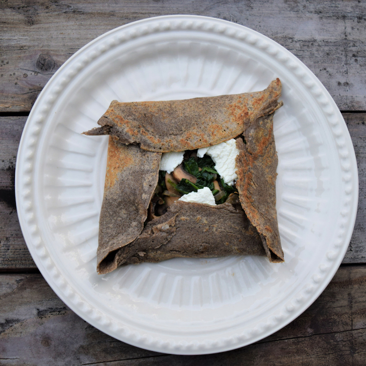 vegetable buckwheat crepe on a white plate on a wood table