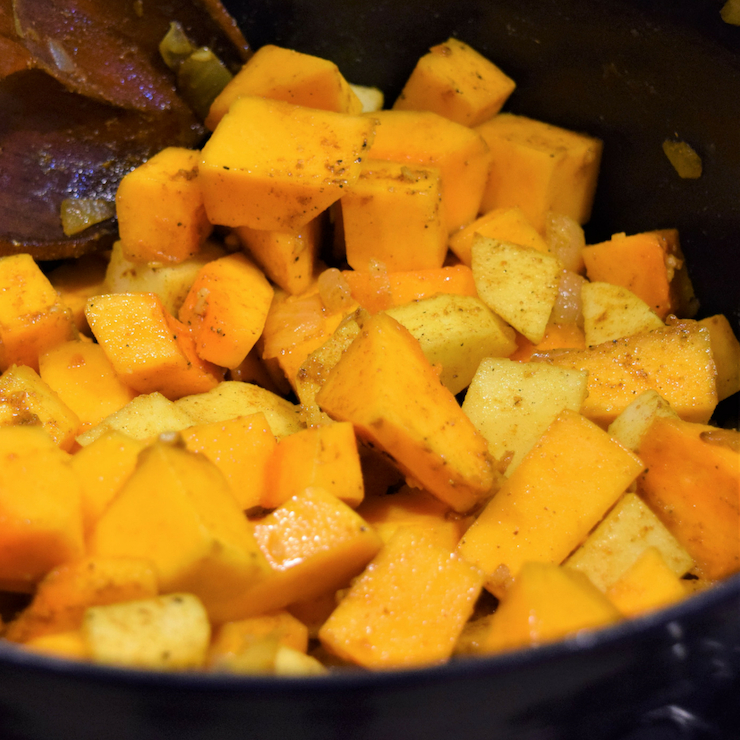 cubes of squash and apples being tossed with seasoning