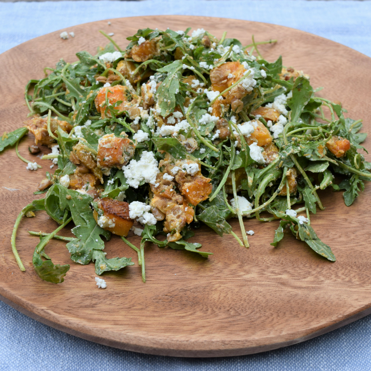 large wooden plate with a heaped arugula salad