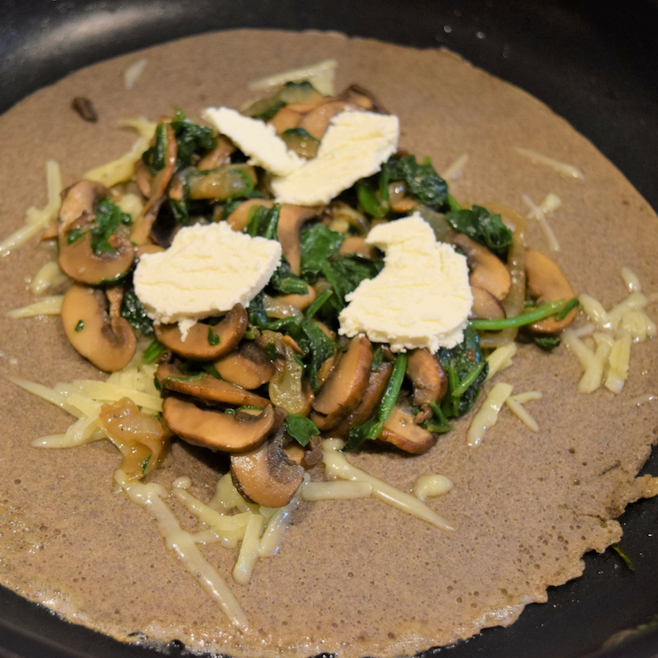 mushrooms onions spinach and goat cheese on a buckwheat crepe