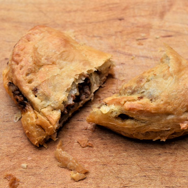two cut halves of a beef empanada on a wood cutting board