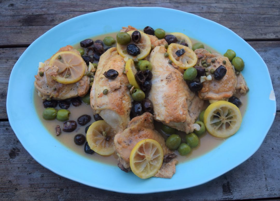 blue ceramic platter of chicken olives and lemon slices