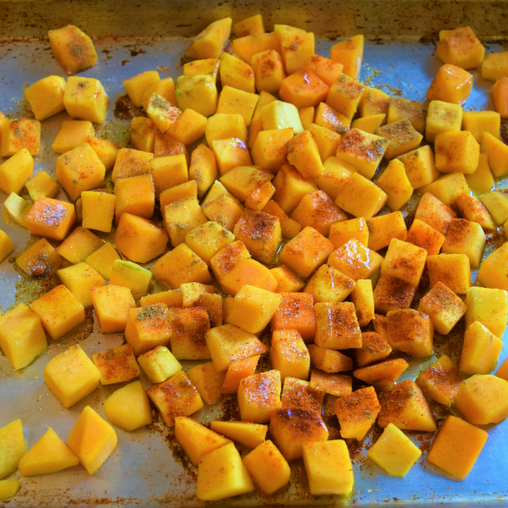 sheet pan of cubed butternut squash with spices and olive oil