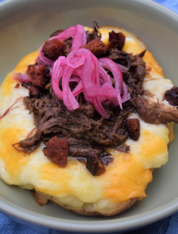 aerial view of pickled red onions topping shredded beef and a cheesy twice baked potato