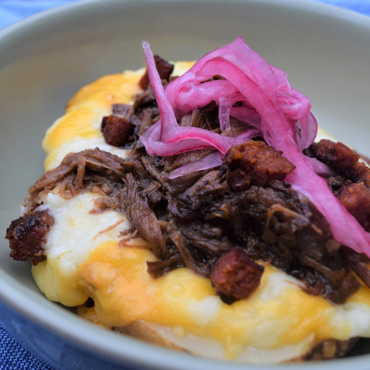 twice baked potato topped with shredded beef and pickled red onions