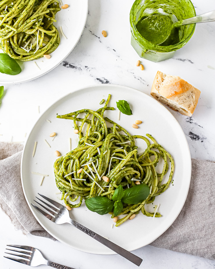 plates of pesto and pasta with baguette and cheese
