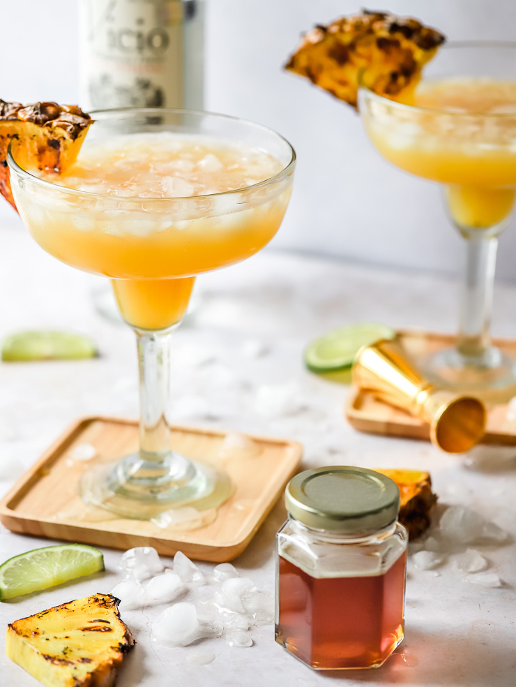pineapple honey and mezcal margarita with grilled pineapple garnish